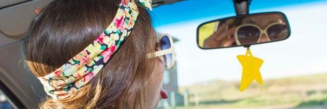 young woman driving a car and looking at herself in the mirror