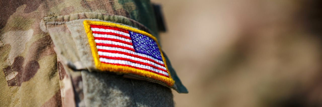 close up of us flag patch on the arm of a soldiers uniform