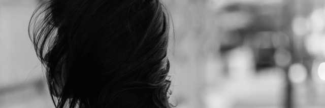 girl with hair blowing in face in black and white