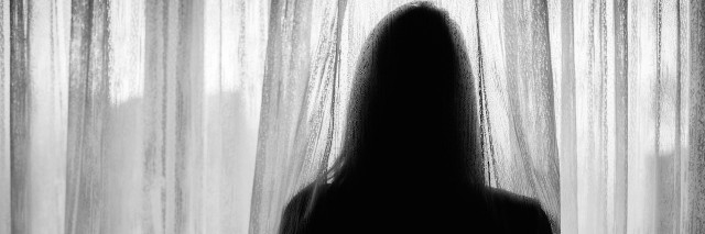 silhouette of woman looking through curtain over window