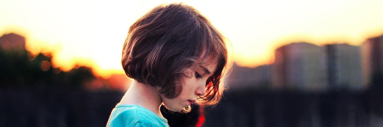 side profile of sad girl in front of sunset