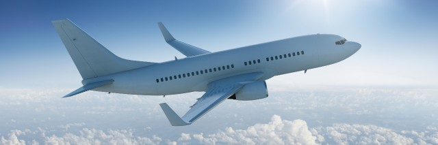 Airplane flies in blue sky.