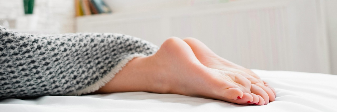 feet showing under blanket on bed