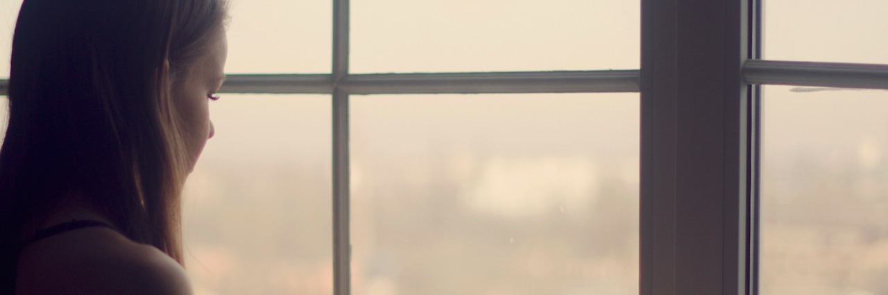 woman holding coffee cup looking out window in the morning