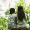 Rear view of two female friends resting in park