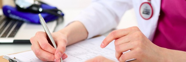 doctor holding pen and signing forms with patient