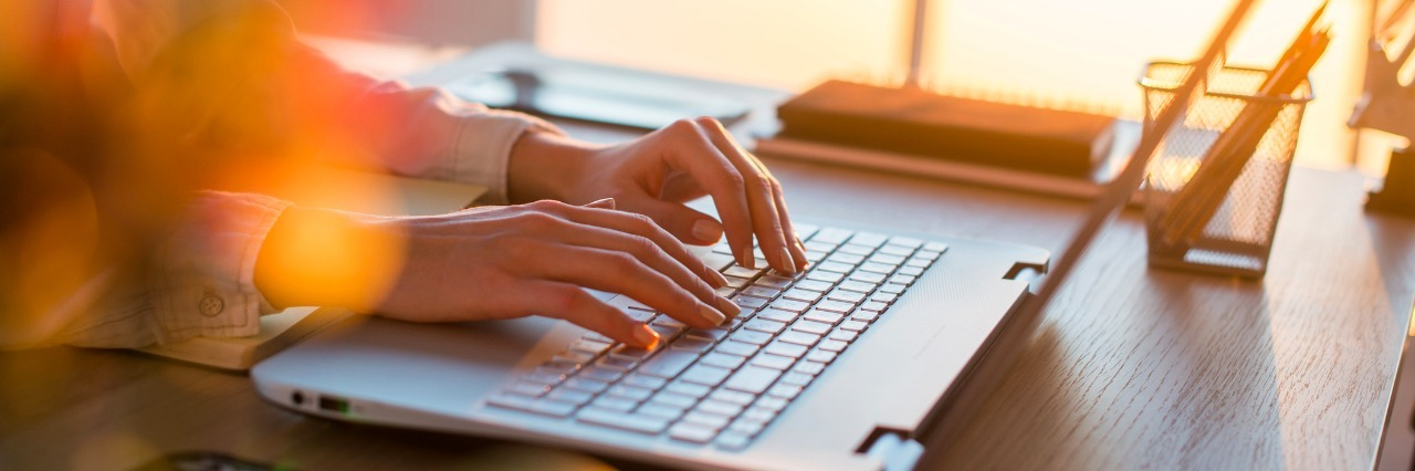 Female teleworker texting using laptop and internet, working online. Freelancer