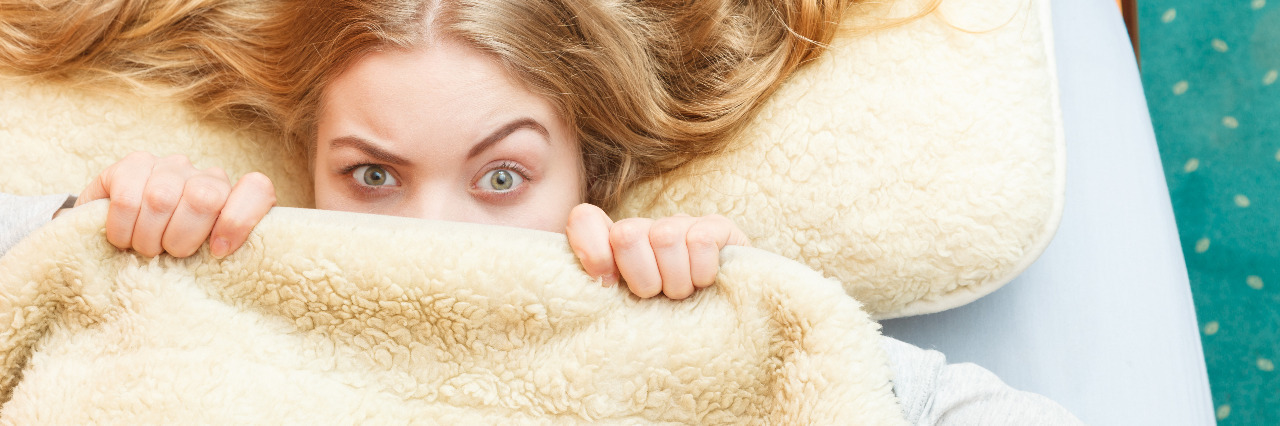 Hiding under a blanket.