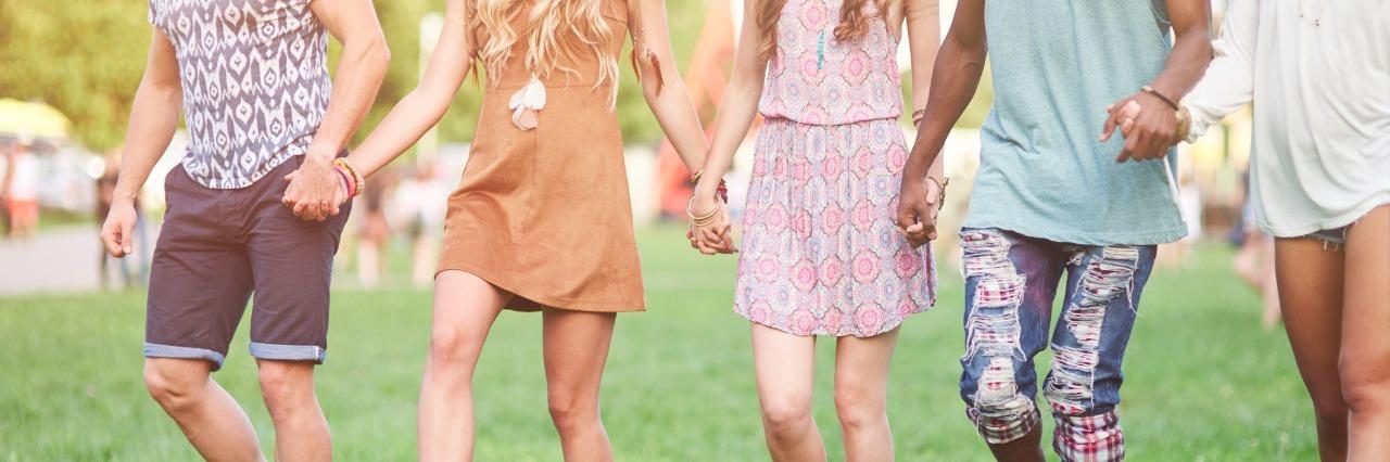Friends walking hand by hand