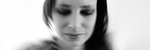 black and white portrait of sad woman in deep thought, thinking, loss, grief, motion blur