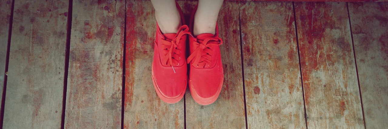 women legs wearing red shoes walking on wooden floor