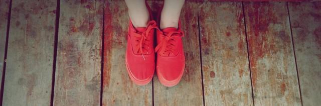 women legs wearing red shoes walking on wooden floor