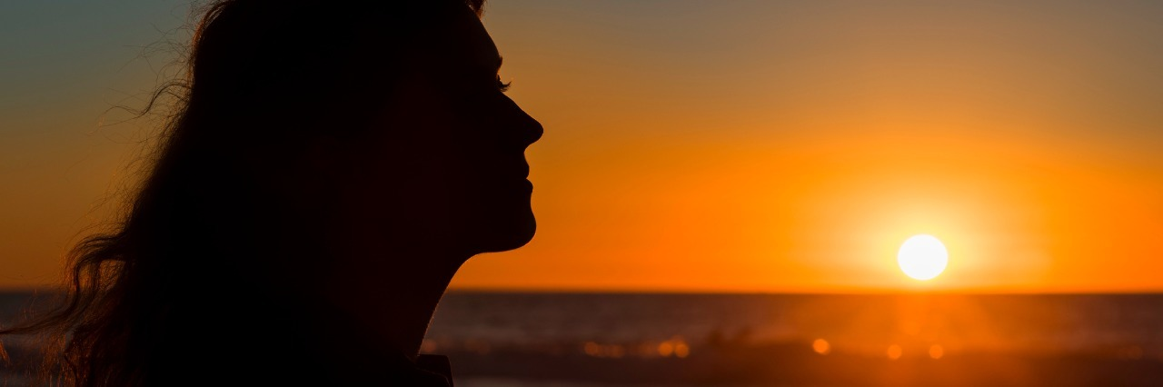 Silhouette profile of young female during sunset in San Diego pacific ocean beach, California