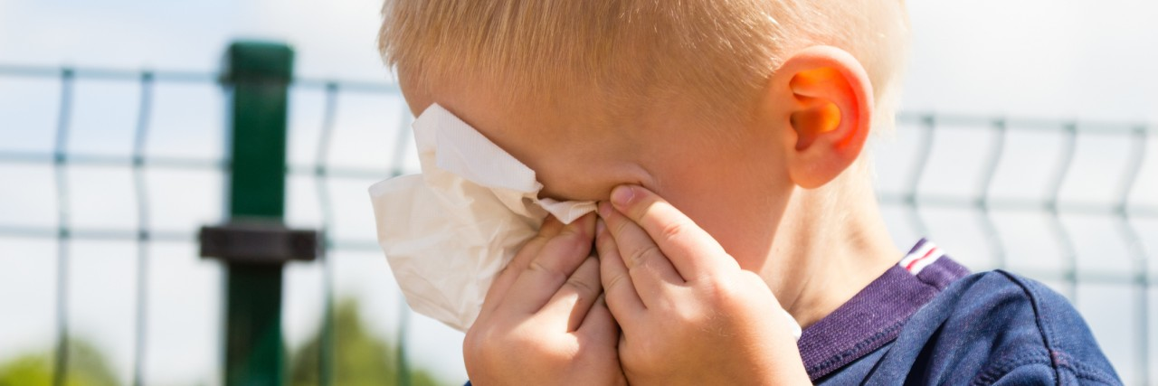 Emotions and feeling. Sad little boy crying, unhappy child wiping his eyes with tissue outdoor