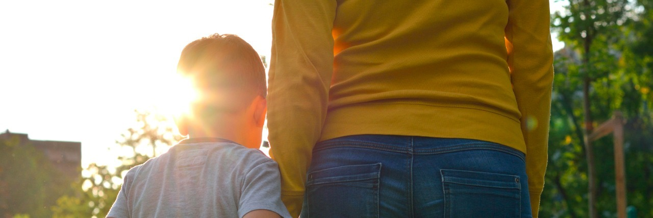 Child holding hands with parent outdoors during sunset