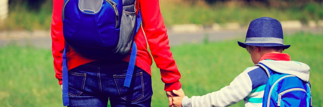 back to school- mother holding hand of little son with backpack outdoors