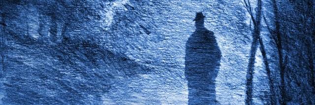 man in a hat in the dark twilight