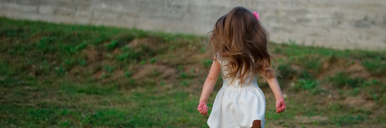 photo of little beautiful running girl outside