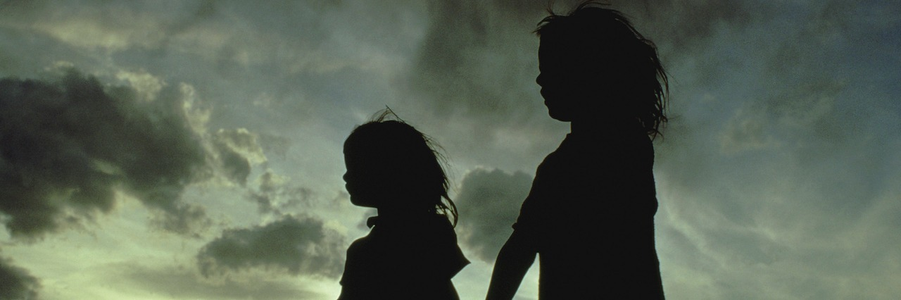 Silhouette of two girls holding hands