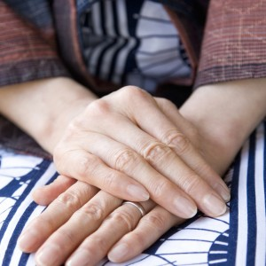 Woman's hands folded in lap, with one hand over the other