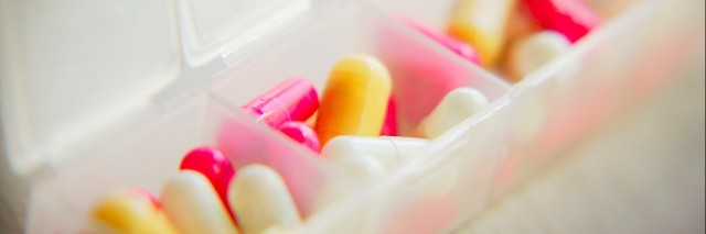 pink and yellow pills in pill organizer