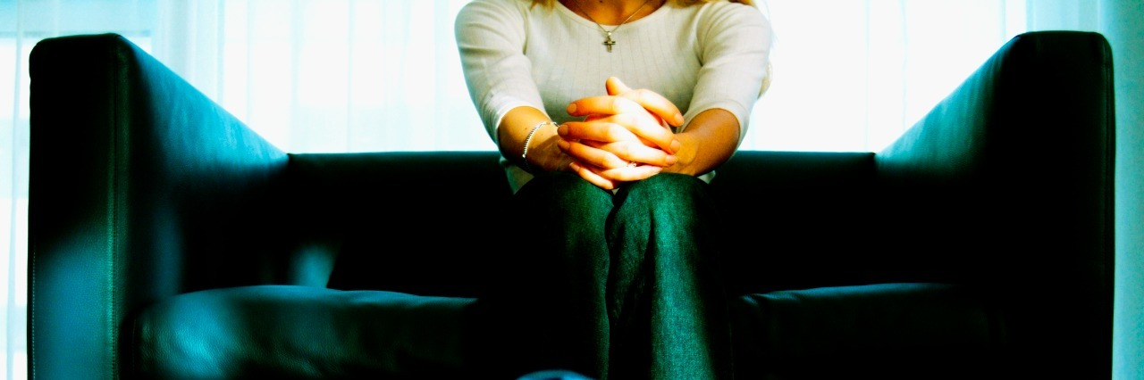 woman sitting on couch with hands folded