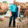 Wedding photo of a woman, her fiance and dog outdoors in front of a river.