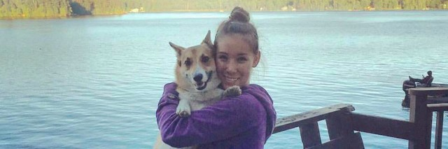 Young woman lifts up and hugs her dog