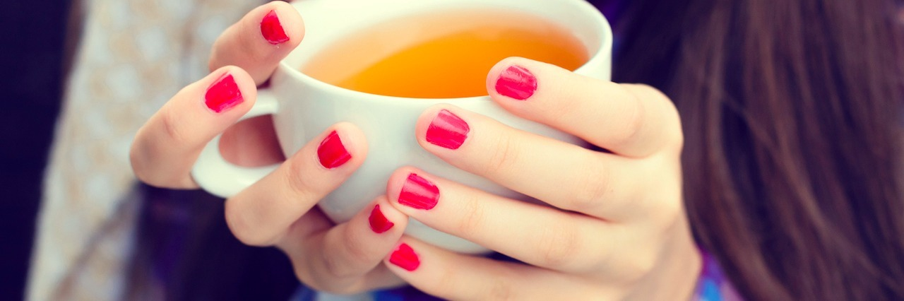 Girl wrapped in a blanket holding a cup of tea close-up