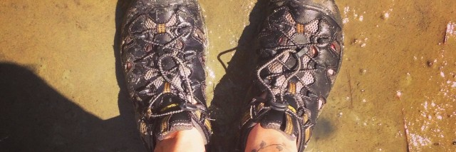 feet wearing hiking shoes standing on wet ground