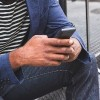 man sitting on steps typing on smartphone