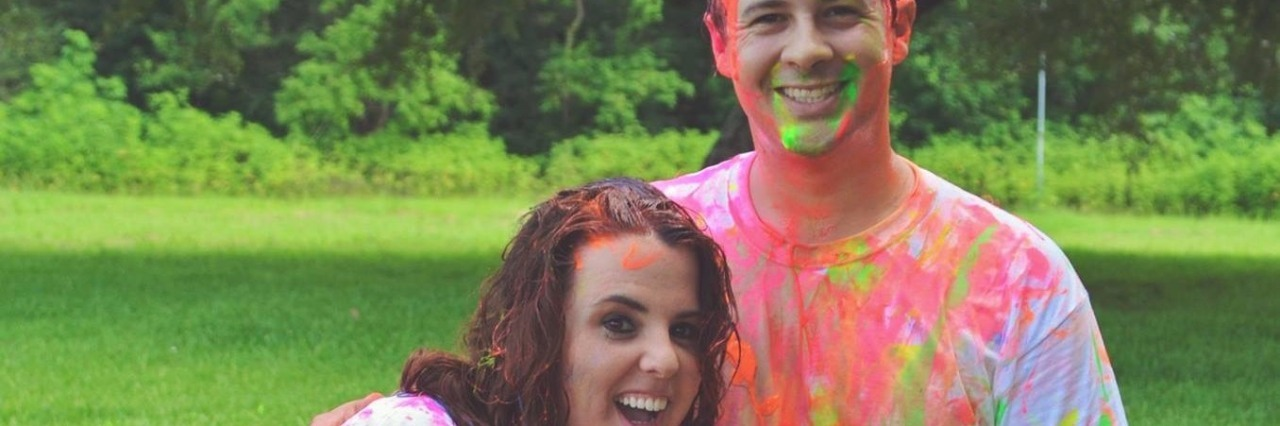 man and woman covered in colorful splatters of paint