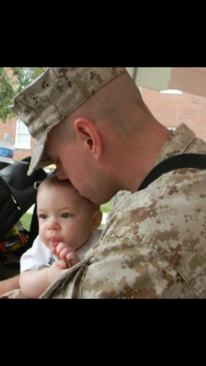 a man in the army kissing his baby