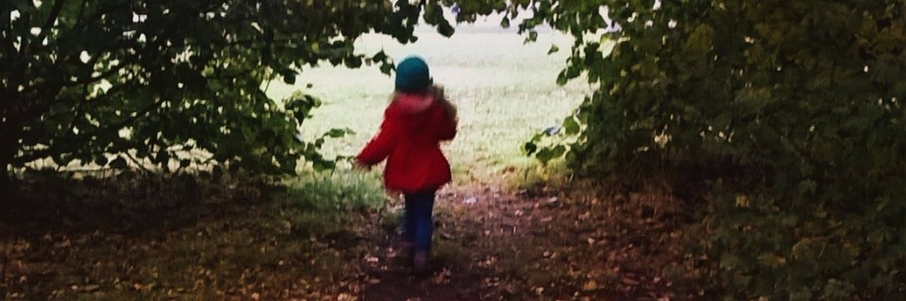 A photo of a child wearing a red jacket, walking through a tree-lined path in a park
