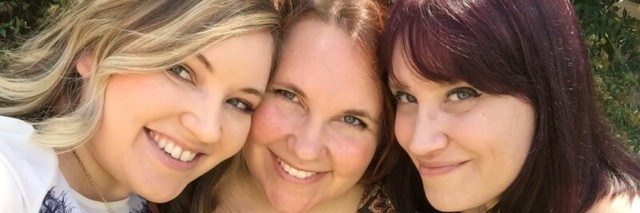 Three woman embracing and smiling for the camera.