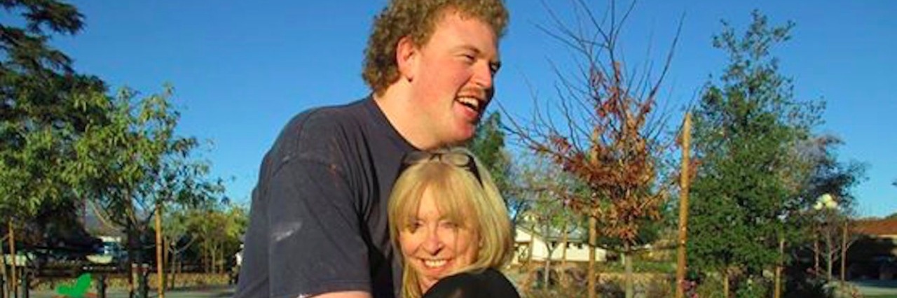 Taylor Cross and his mom Keri, hugging outdoors