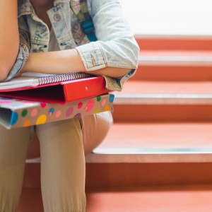 student with binders on lap sitting on stairs