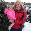 Mom holding daughter while next to trees and a snowy ground
