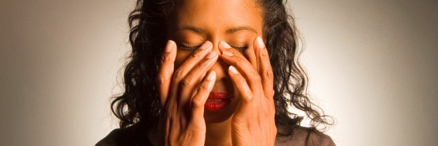 woman holding hands on face with migraine