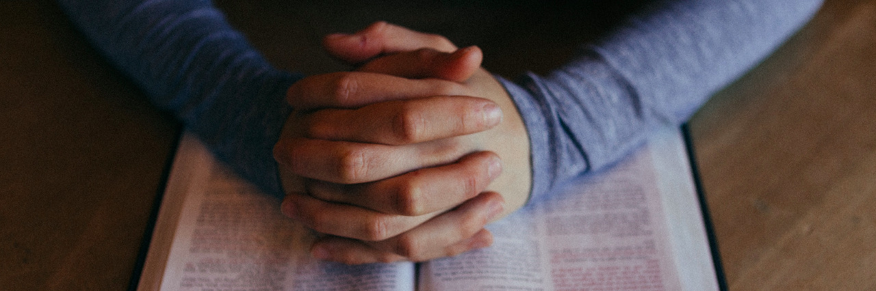 mans hands folded in prayer over his Bible