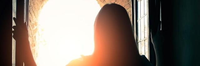Silhoutte of woman opening window
