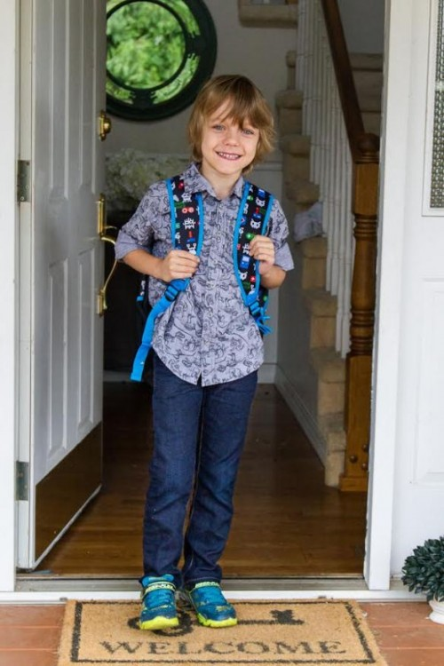 boy standing in doorway wearing backpack