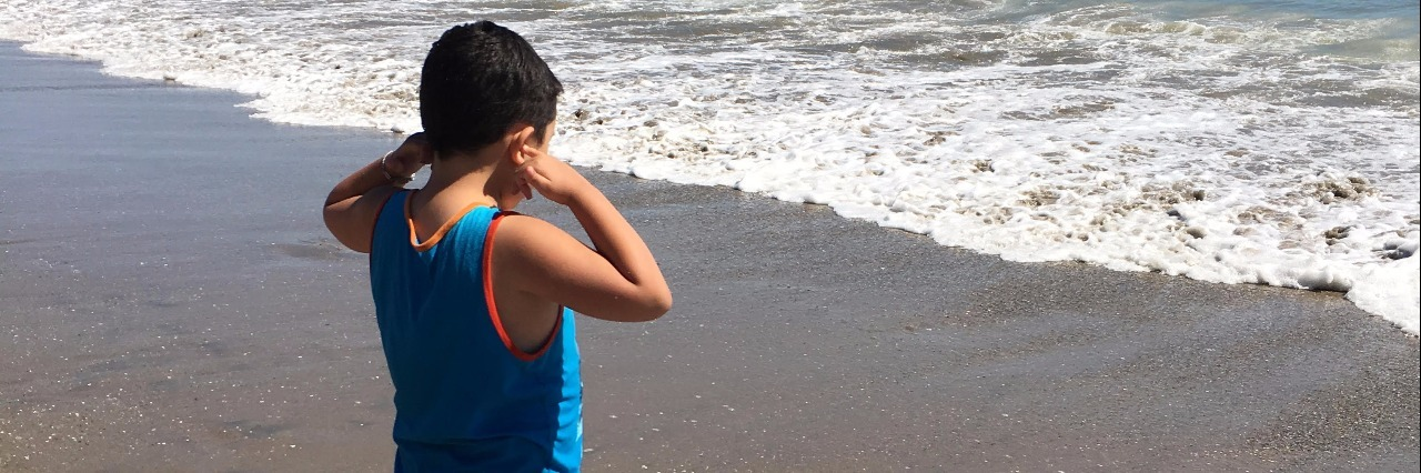 little boy with autism covering his ears at the beach