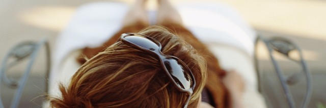 woman with sunglasses on head lying on a lounge chair