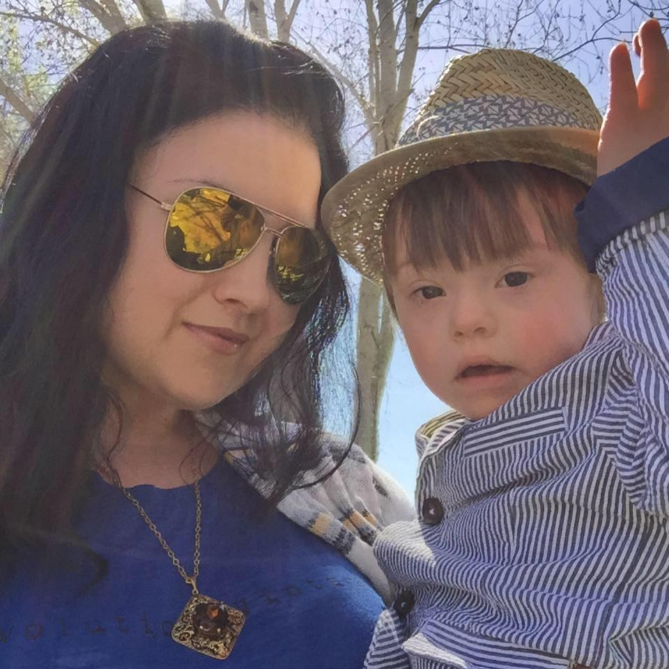 Mom wearing sunglasses, holding son wearing a hat