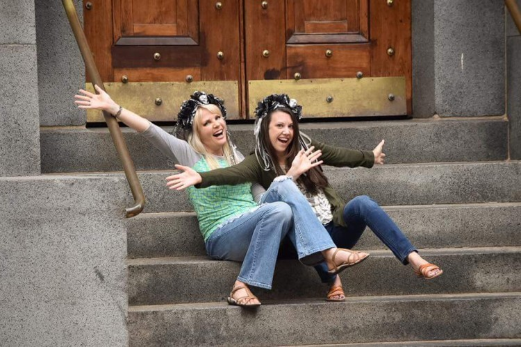 Melissa and her friend smiling while sitting on stairs