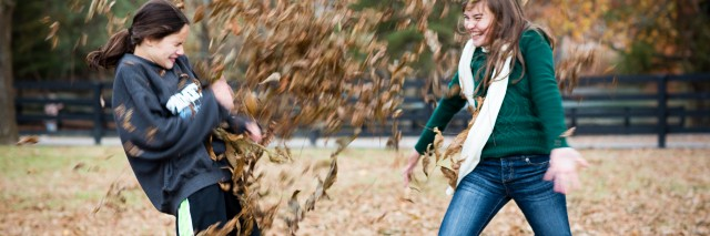 Two girls playing in the autumn leaves outdoors