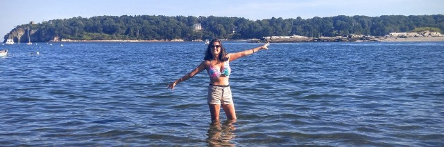 girl standing in lake with arms out