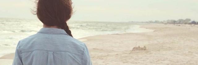 woman in jean jacket walking on the beach