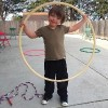 Boy standing in backyard with hula hoop